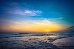 Sunset Background Ocean. Tropical Sunlight and Summer Sunset View. Colorful Background Sunset. Blue Waves near sea Resort. Sea sunset Background. Colorful Beach with Surfers on the Horizon. Landscape