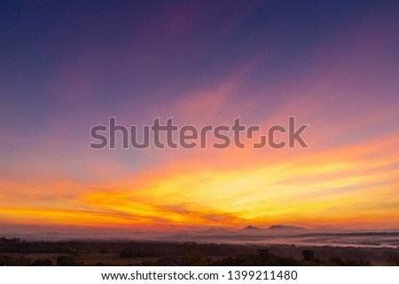 Sunset background with wonderful golden yellow sky, Amazing purple and orange sky in evening during the sun going down above the mountain at countryside, Chae Hom District, Lampang, Thailand. #1399211480
