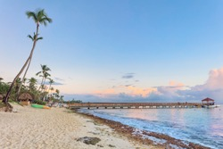 Sunset beach of La Romana, Dominican Republic with long wooden pier