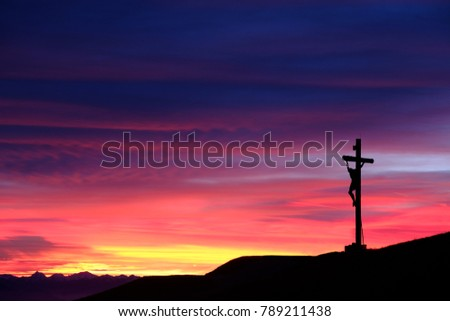 Sunset behind a mountain top cross in the Dolomites