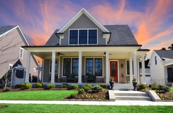 Sunset behind a Single-Family Suburban Craftsman House with Big Front Porch, White Pillars, and a Red Front Door.