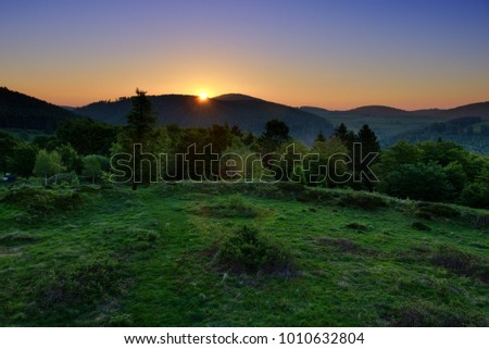Sunset behind a wooded mountain range with flat grassy hilltop in the foreground