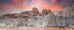 Sunset behind Cathedral rock, rising above fresh snow in the trees along Oak Creek in the red rock country near Sedona, Arizona