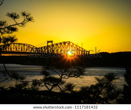 Sunset behind landmark bridge in Québec, Canada with St. Lawrence Stream in the foreground