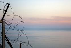 Sunset behind the barbed wire at the sea. Barbed wire fence at sunset. Barbed wire over the sea.