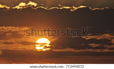 Sunset behind the clouds #713494072