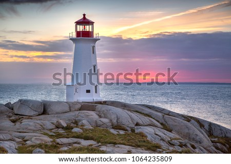 Stock Photo Sunset behind the lighthouse at Peggy's Cove near Halifax, Nova Scotia Canada.