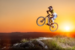Sunset. Biker flying on a mountain bike on the precipice of hill against evening sky with bright sun. Cyclist is wearing sportswear helmet and glasses. Extreme sport