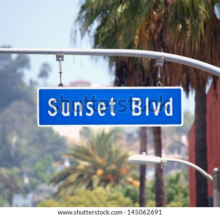 Sunset Blvd street sign with palm trees in Hollywood, California.