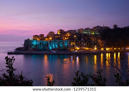 Sunset capture of the old town and fortress of Ulcinj in southern Montenegro.  Each night the ramparts are illuminated with various colors.  . Blue lights on ramparts and purple sky  - Shutterstock ID 1239571315