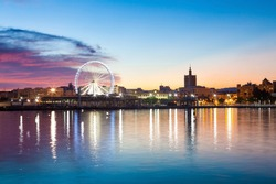 Sunset cityscape in the marina bay port of Malaga, with ferris wheel in the background.