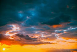 Sunset Cloudy Sky With Fluffy Clouds. Sunset Sky Natural Background. Sunrays, sunray, ray, Dramatic Sky. Sunset In Yellow, Orange, Pink Colors.