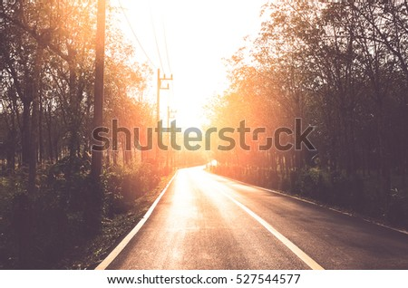 Sunset country road. Travel adventure and transportation concept. Vintage tone filter color style.