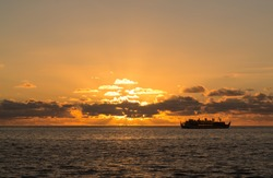 Sunset cruise ship sails on horizon as the sun sets slowly behind clouds off Oahu in Hawaii
