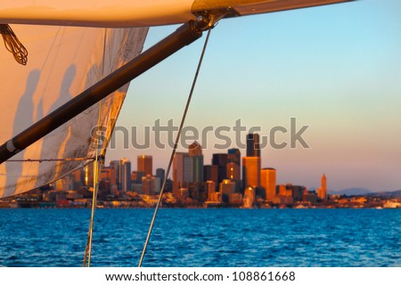 Sunset cruise with a sail framing the Seattle skyline in the background.  You can see shadows on the sail of people on the boat.  Copy space