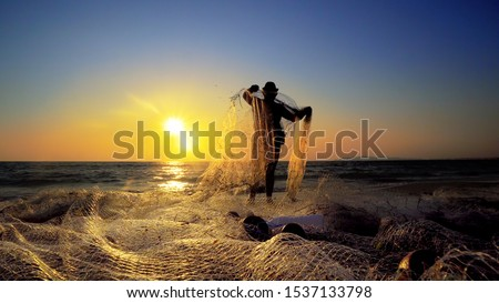 Sunset fishermans pulling net catching fish on ocean, cinematic steadicam shot #1537133798