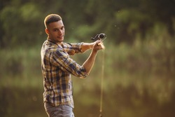 Sunset fishing. Cropped portrait of young man spending time outdoors in countryside near river and fishing. Active weekend. Resting on warm summer day. Concept of leisure time activity, ad