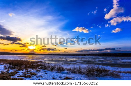 Sunset forest lake snow landscape. Lake sunset sky clouds