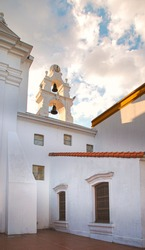 Sunset from a church courtyard with a bell tower. Cloudy afternoon from chapel exterior with bells. Serenity, calmness and serenity concept. Religion architecture