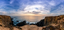 sunset from the top of a cliff overlooking the atlantic ocean and the waves crashing on the rocks