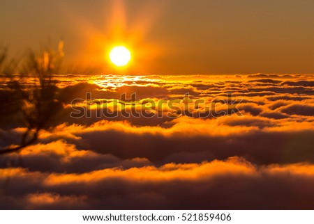 Sunset from the  top of mountain over the clouds - Shutterstock ID 521859406