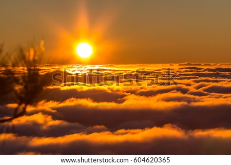 Sunset from the  top of mountain over the clouds - Shutterstock ID 604620365