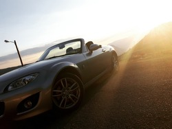Sunset front view of silver gray convertible car, mountain valley in background