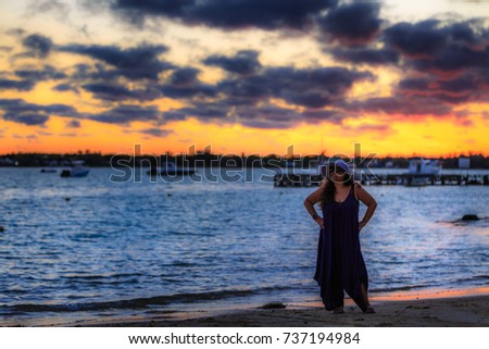 Sunset girl looking at camera with a classic ocean view in the background.