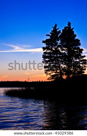 Sunset glow beyond a northern Canadian lake at twilight with the silhouette of trees in the foreground.