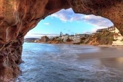 Sunset hits homes along Pearl Street Beach through a rock keyhole in Laguna Beach, California, USA