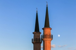 Sunset horizontal landscape: two brick minarets of the mosque in Chishmy with a blue evening sky and the moon in the background