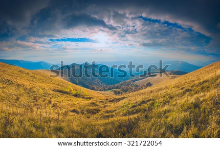 Sunset in a Carpathian mountains with colorful dramatic sky and yellow autumn grass on a meadow #321722054