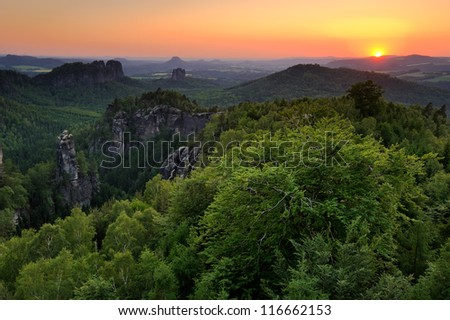 Sunset in a landscape with the rocky cliffs, beech forest under orange bright sky, Germany