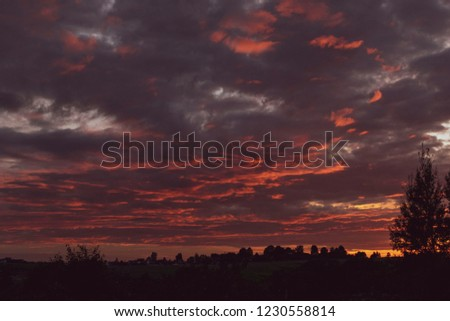 sunset in bloody cloudy sky above the village. beautiful countryside landscape #1230558814