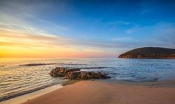 Sunset in Cala Violina bay beach in Maremma, Tuscany. Travel destination in Mediterranean sea. Italy, Europe.