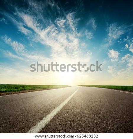 sunset in clouds over asphalt road #625468232