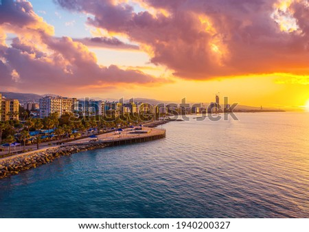 Sunset in Cyprus. View of Limassol coast at sunset. View of Limassol from the top. Promenade of the Mediterranean sea. Parasailing over the Mediterranean. Parachuting. Evening landscape of Cyprus.