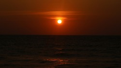 Sunset in dark orange sky in the evening. Sundown background in the evening at the sea, beach sundown single focus