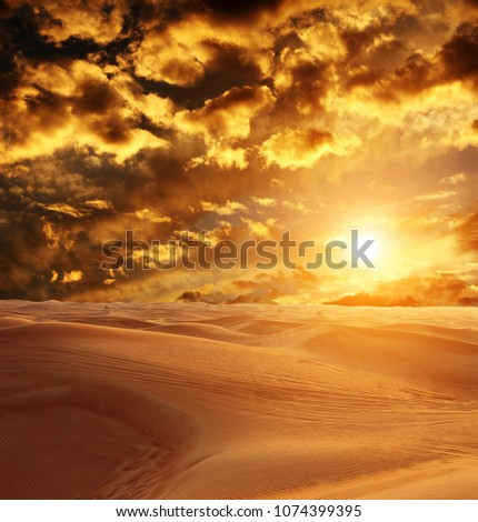 Sunset in desert. Beautiful landscape with sand dunes, cloudy sky and sun