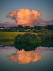 Sunset in Dunhill, County Waterford with reflections in the water of a lake. spectacular clouds.