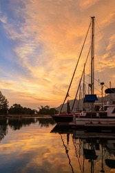 Sunset in harbor yacht marina. Sailing and motor yachts and catamarans anchored near to the pier. Hulls of yachts against the sunset sky and dramatic clouds