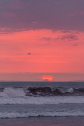 Sunset in Jaco Beach, Costa Rica. Waves in the foreground and the sun hiding behind a small mountain.