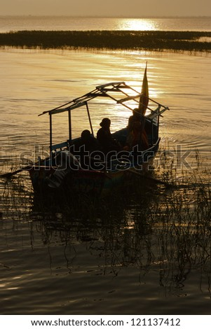 Sunset in Lake Awassa, Ethiopia. People sailing near the shore