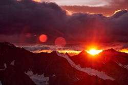 Sunset in mountains. Reflection of red sun on mountain snow peaks and clouds. Altai, Belukha area.