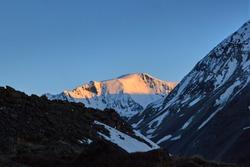 Sunset in mountains. Reflection of red sun on mountain snow peaks, Fann, Pamir Alay, Tajikistan