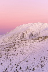 Sunset in mountains. Winter scenery. Beautiful pink and white sky, windy weather. Pink, purple and blue mild pastel colors