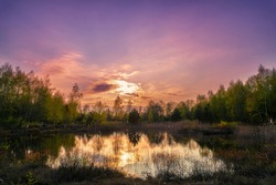 Sunset in purple mood on a lake with reflections on the water