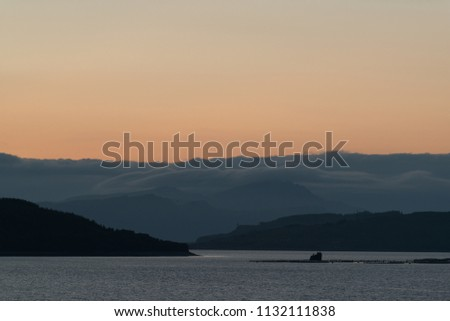 Sunset in Scottish Highlands: mountains covered with clouds, orange sky and a lake with silvery water