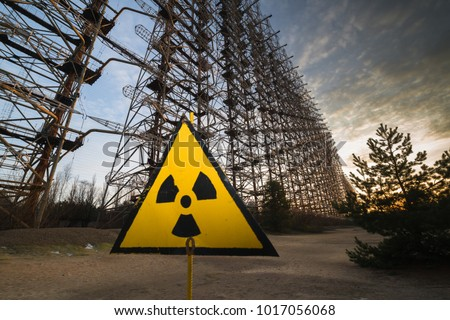 Sunset in Soviet Radar System Duga near Chernobyl Nuclear Power Plant. Nuclear sign in front #1017056068
