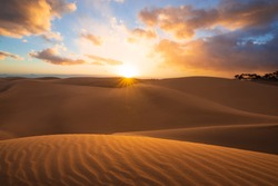 Sunset in the desert, sun and sun rays, Beautiful clouds on blue sky. Golden sand dunes in desert in Maspalomas, Gran Canaria, Canary islands, Spain